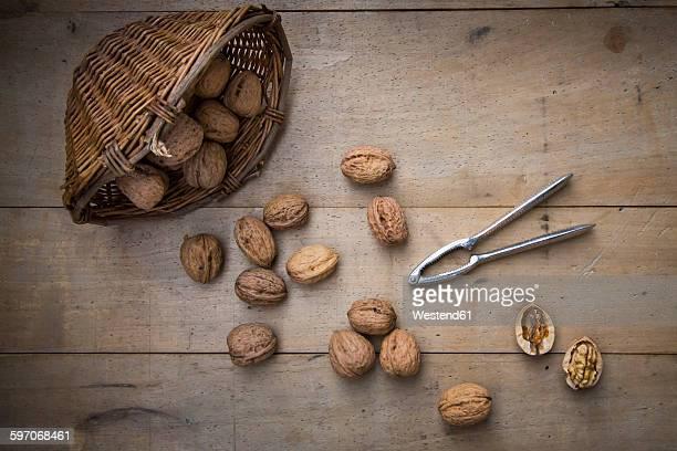 Wickerbasket, walnuts and nutcracker on wood