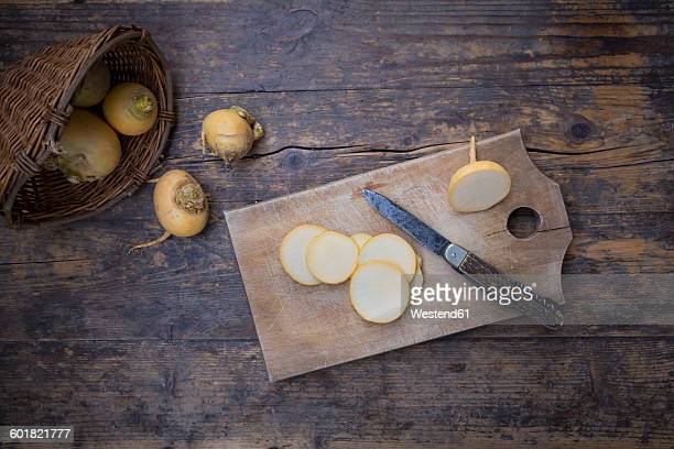 wickerbasket, whole and sliced swedes, wooden board and a knife on dark wood - nabo sueco fotografías e imágenes de stock