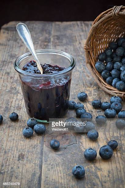 Wickerbasket with blueberries (Vaccinium myrtillus) and glass of blueberry jam on wooden table