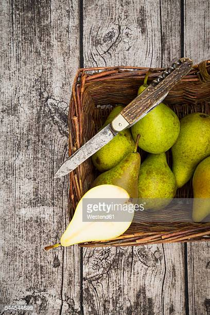 Wickerbasket with pears and pocket knife on grey wood
