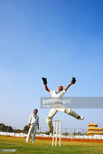 Wicket keeper jumping in jubilation