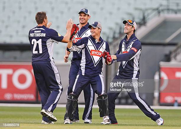 Wicket keeper Peter Hanscombe of the Bushrangers celebrates taking a catch as bowler Darren Pattinson Clint Mckay and Glenn Maxwell join him during...