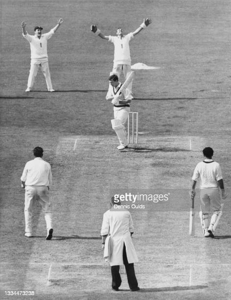 Wicketkeeper Jim Parks of England raises his arms in celebration after catching Graham McKenzie of Australia to dismiss him for 4 off the bowling of...