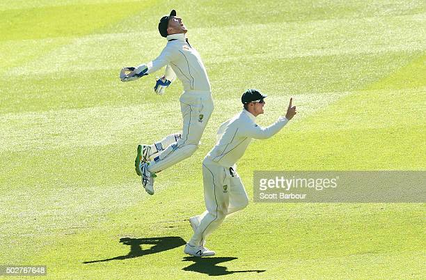 Wicketkeeper Peter Nevill of Australia celebrates after taking a catch to dismiss Denesh Ramdin of the West Indies as captain Steven Smith looks on...