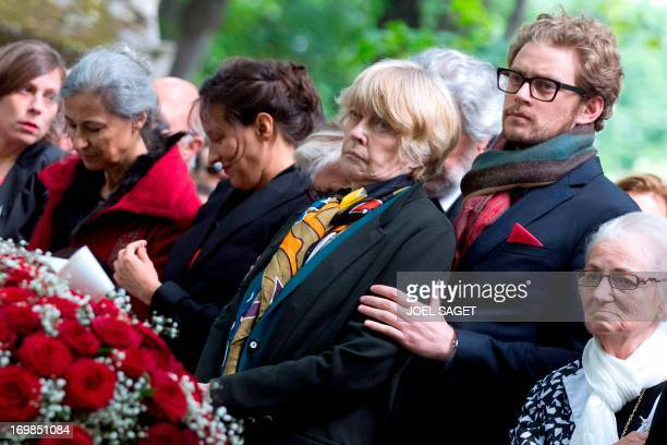 Widdow of late Guy Carcassonne Claire Bretecher and her son Martin stand on June 3 2013 at the Montmartre cemetery in Paris during the funeral of the...