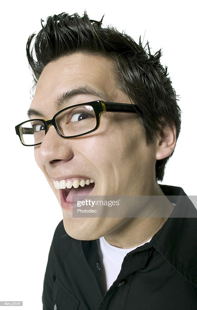 wide angle close up of a young adult male in glasses as he smiles and makes a funny face : Foto de stock