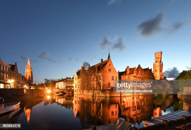 Wide angle, full length image of romantic Rozenhoedkaai canal, Belfry of Bruges and Church of our Lady spire illuminated at late dusk in Bruges, Flanders, Belgium