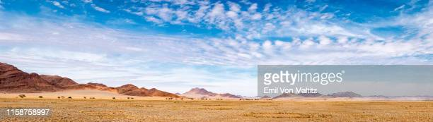 wide angle landscape colour image with scattered mountain ranges and a blue sky filled with white stratocumulus clouds. route 202, at the edge of the namib-naukluft national park, namibia. - ancho fotografías e imágenes de stock