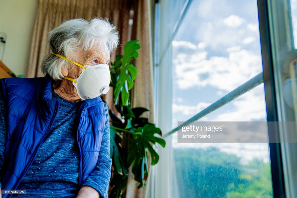 Wide Angle Low Shot Distraught Elderly Senior Caucasian Woman Looking Out the Window Feeling Loneliness Wearing an n95 Protective Face Mask To Prevent the Spread of COVID SARS nCoV 19 Coronavirus Swine Flu H7N9 Influenza Illness During Cold and Flu Season : Stock Photo