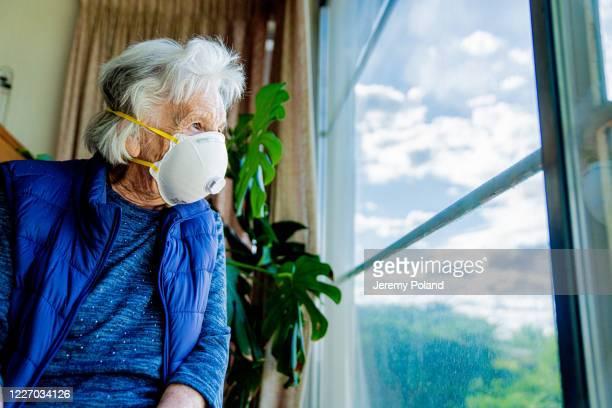vidvinkel low shot upprörd äldre senior kaukasiska kvinna tittar ut genom fönstret känsla ensamhet bär en n95 skyddande ansiktsmask för att förhindra spridning av covid sars ncov 19 coronavirus svin influensa h7n9 influensa sjukdom under förkylning - munskydd ensam bildbanksfoton och bilder