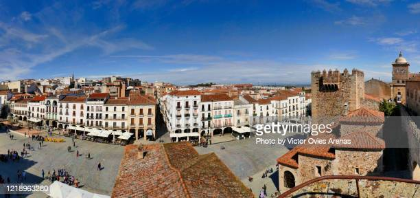 wide angle panoramic view of the main square (plaza mayor) and bujaco tower from the ramparts. old town. caceres - victor ovies fotografías e imágenes de stock