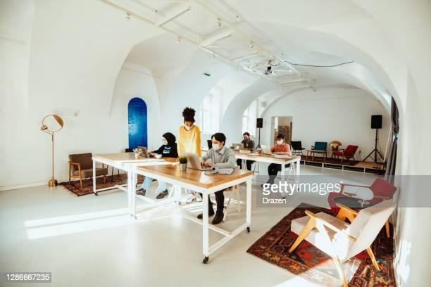 photo grand angle des personnes multiethniques dans le bureau partagé pendant la pandémie de deuxième vague de coronavirus - hijab feet photos et images de collection