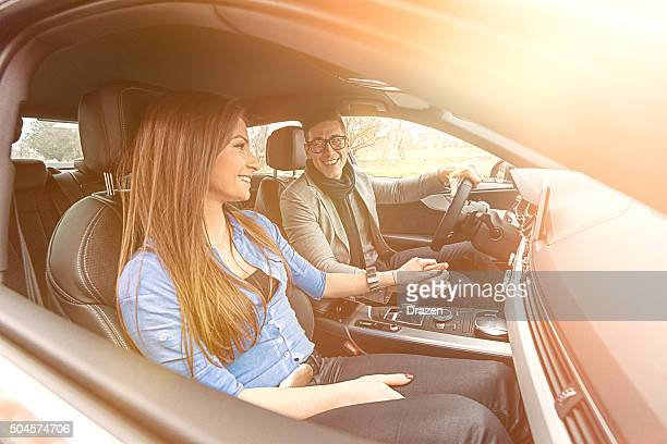 Wide angle portrait of attractive young couple driving luxury car