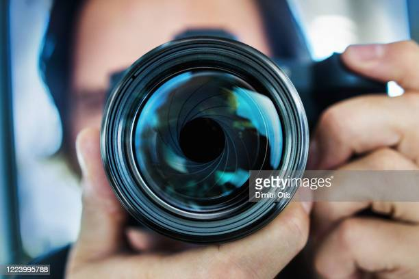 wide angle portrait of man holding camera, closeup on lens - wide angle stock pictures, royalty-free photos & images