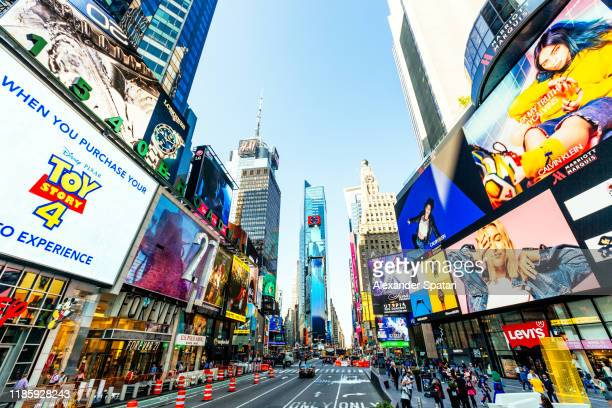 wide angle shot of times square on a sunny day, new york, usa - advertisement stock pictures, royalty-free photos & images