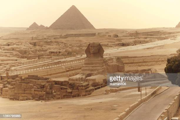 wide angle sphinx of giza with the great pyramid of giza background and vintage filter process - egypt stock pictures, royalty-free photos & images