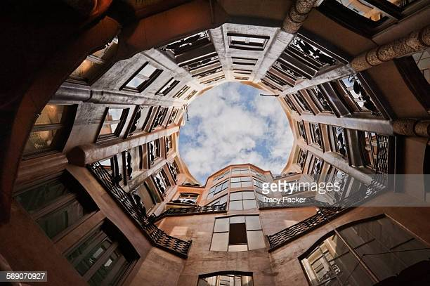 A wide angle view looking directly up to the sky from the inner courtyard inside 'La Pedrera' the Modernista apartment block designed by the Catalan...