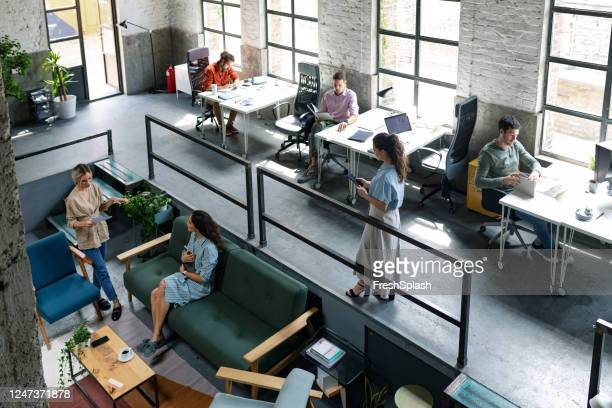 wide angle view of a modern loft open space office with businesspeople working in it - coworking stock pictures, royalty-free photos & images