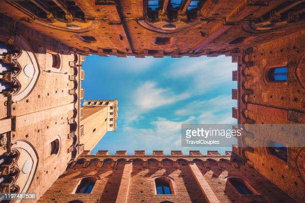 wide angle view of famous torre del mangia at palazzo pubblico in siena, italy - italy stock pictures, royalty-free photos & images