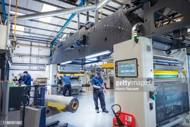 wide angle view of food packaging machine and workers in print factory - place of work stock pictures, royalty-free photos & images