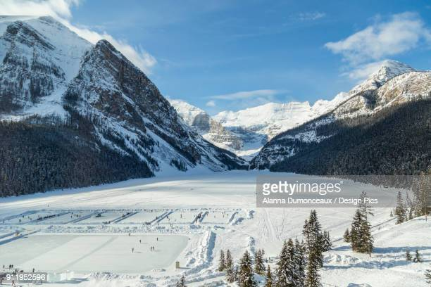 a wide angle view of lake louise from the upper floor of chateau lake louise resort in the winter surrounded by snow capped mountains and filled with skaters on the ice rinks carved into the frozen lake - chateau lake louise stock photos and pictures