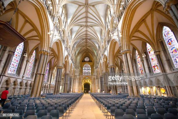 wide angle view of lincoln cathedral showing the decorative vaulted ceiling and rows of chairs inside. - nave stock pictures, royalty-free photos & images