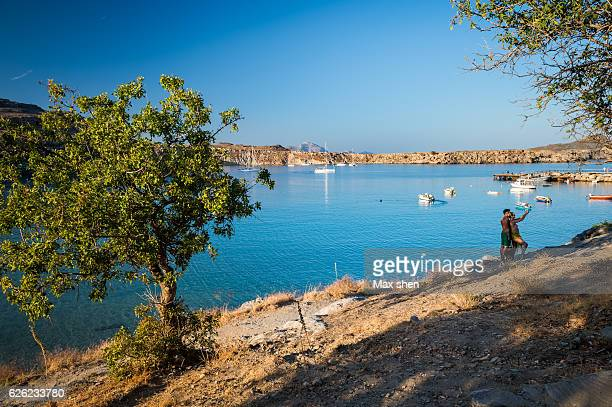 wide angle view of the lindos main beach on rhodes island, greece. - lindos stock photos and pictures