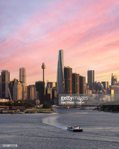 wide cityscape of sydney at sunset showing the grown tower, international towers and others. - sydney stock pictures, royalty-free photos & images