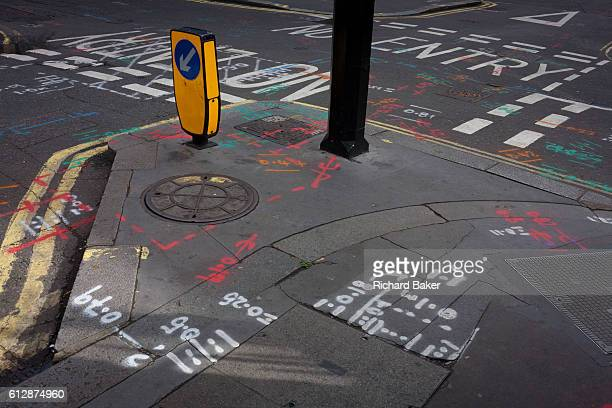 A wide detail of a street landscape at a road junction with construction markings on 29th September 2016 in Soho central London Various coded lines...