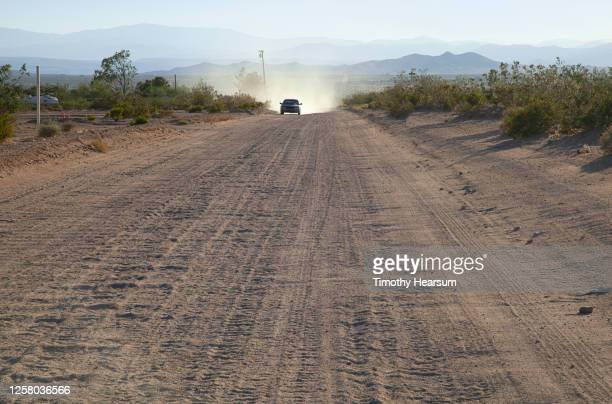 wide dirt road with approaching car creating dust; mountain range and sky beyond - timothy hearsum stock-fotos und bilder
