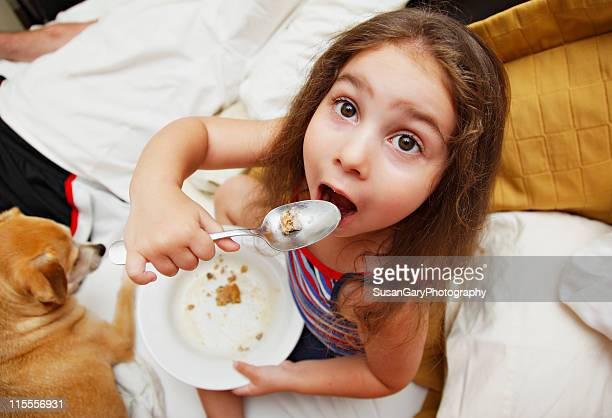 wide eyed girl eating ice cream and cookies - dog eats out girl stock pictures, royalty-free photos & images
