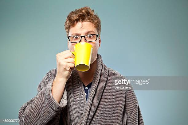 Wide eyed young male drinking coffee from a yellow mug