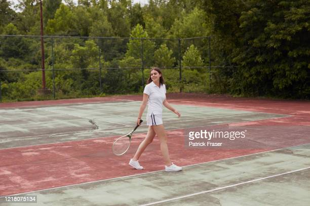wide full length of girl walking on run down hard tennis court holding a racket - racquet stock pictures, royalty-free photos & images