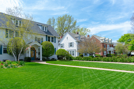 Wide green front lawns in traditional suburban residential neighborhood 1141528775