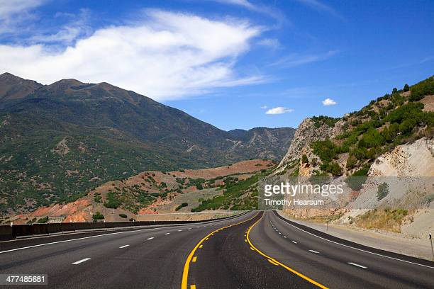 wide highway with passing lane through mountains - timothy hearsum stock-fotos und bilder