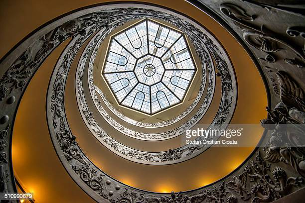 Wide image of Vatican Museum staircase viewed from down to ceiling.