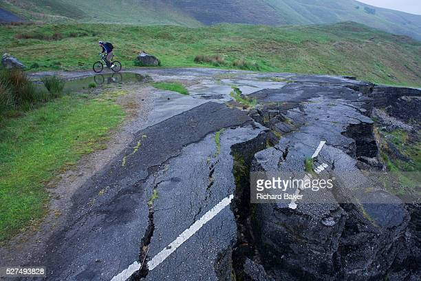 A wide landscape of damp hillsides and moorland as a lone cyclist struggles uphill near a road landslide at the foot of Mam Tor in the in the...