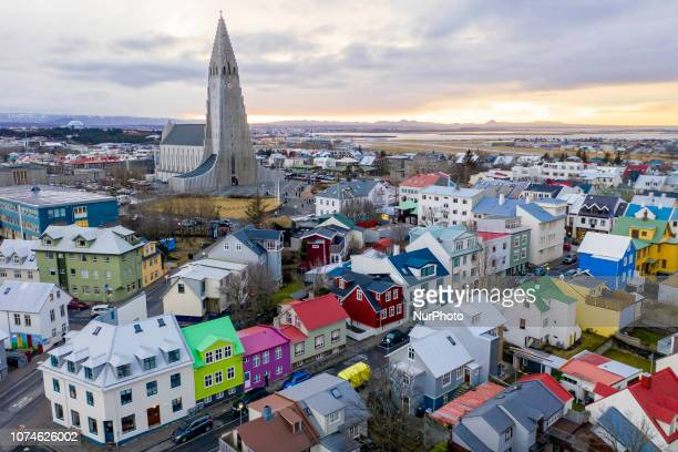 Wide landscape views of buildings, cars, people, homes, apartments, mountains, streets, water, and businesses are seen in Reykjavik, Iceland on...