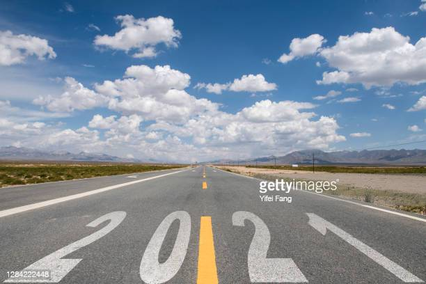 wide open highway under a blue cloudy sky with 2021 on road surface - 2021 stock pictures, royalty-free photos & images