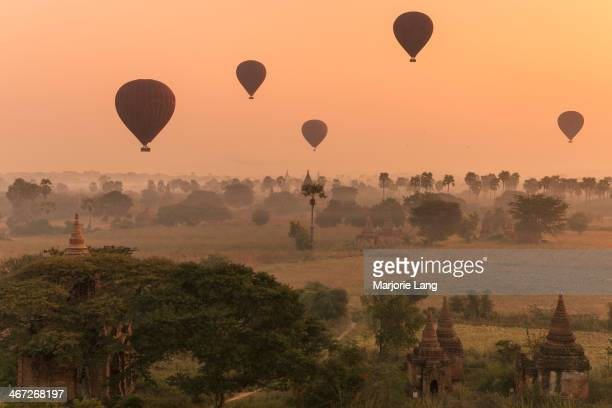 CONTENT] Wide panoramic view of Bagan plains filled with hot air balloons in the sky and Buddhist pagodas and ruins in the warm tones of a misty...