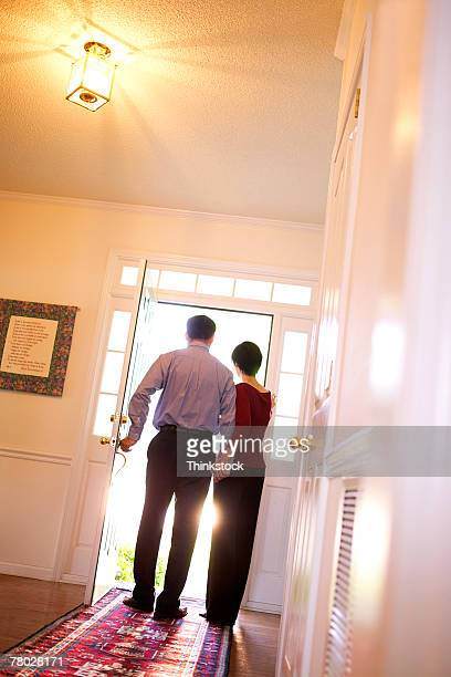 Wide rear view of a couple welcoming someone at the front door of their home