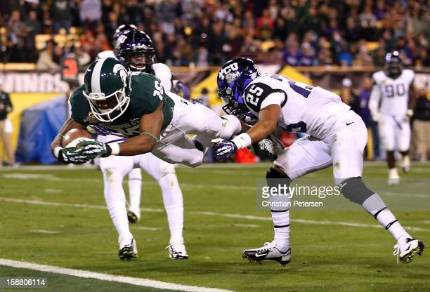 Wide receiver Aaron Burbridge of the Michigan State Spartans dives into the end zone to score a 15-yard touchdown reception past cornerback Kevin...