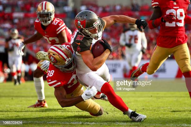 Wide receiver Adam Humphries of the Tampa Bay Buccaneers drags strong safety Antone Exum of the San Francisco 49ers into the end zone to score at the...