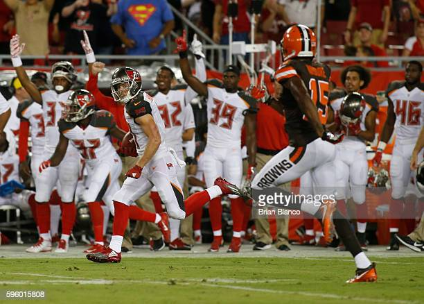 Wide receiver Adam Humphries of the Tampa Bay Buccaneers evades wide receiver Marlon Moore of the Cleveland Browns on his 72 yard punt return for a...