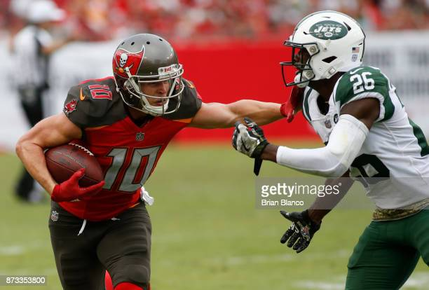 Wide receiver Adam Humphries of the Tampa Bay Buccaneers fends off free safety Marcus Maye of the New York Jets after hauling in a pass from...