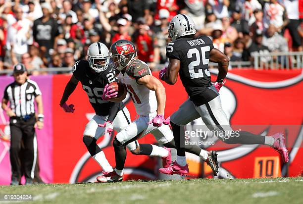 Wide receiver Adam Humphries of the Tampa Bay Buccaneers finds room to run between cornerback David Amerson and cornerback DJ Hayden of the Oakland...