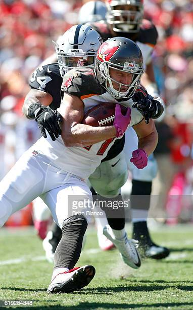 Wide receiver Adam Humphries of the Tampa Bay Buccaneers is brought down by outside linebacker Perry Riley of the Oakland Raiders during the ***...