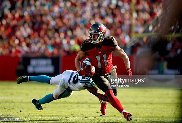Wide receiver Adam Humphries of the Tampa Bay Buccaneers runs for a gain of 17 yards to bring up first and goal while getting pressure from defensive...