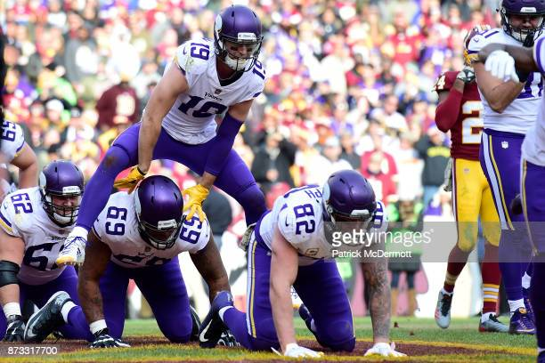 Wide receiver Adam Thielen of the Minnesota Vikings celebrates with teammates after scoring a touchdown during the second quarter against the...