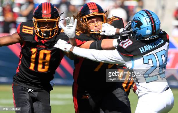 Wide receiver Adonis Jennings and offensive tackle Storm Norton of the Los Angeles Wildcats block safety Tenny Adewusi of the Dallas Renegades for...